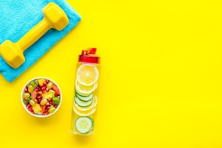 Photo pour Healthy lifestyle, healthy habits. Detox water, fruit salad, sport equipment dumbbells on yellow background top view space for text - image libre de droit