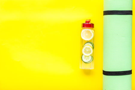 Photo pour Healthy fruit water for sport, fitness. Bottle of water with lemon and cucumber near sport equipment on yellow background top view. - image libre de droit
