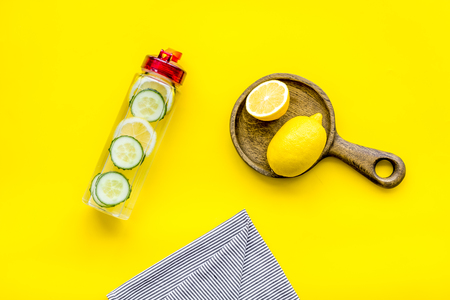 Photo pour Make detox fruit water. Slices of lemon and cucumber in bottle on yellow background top view. - image libre de droit