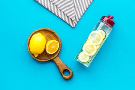 Photo pour Make detox fruit water. Slices of lemon and cucumber in bottle on blue background top view copy space - image libre de droit