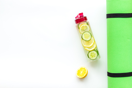Photo pour Healthy fruit water for sport, fitness. Bottle of water with lemon and cucumber near sport equipment on white background top view copy space - image libre de droit