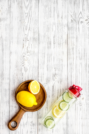 Photo pour Detox infused water with slices of lemon and cucumber in bottle on white wooden background top view copy space - image libre de droit