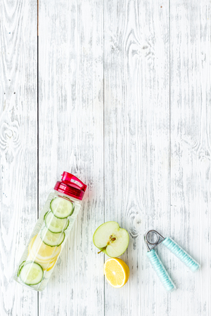 Photo pour Healthy fruit water for sport, fitness. Bottle of water with lemon and cucumber near sport equipment on white wooden background top view copy space - image libre de droit