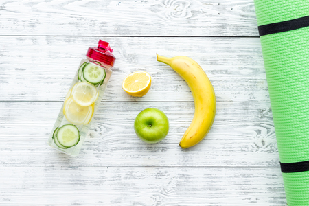 Photo pour Healthy fruit water for sport, fitness. Bottle of water with lemon and cucumber near sport equipment on white wooden background top view. - image libre de droit