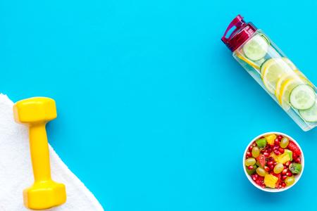 Photo pour Healthy lifestyle, healthy habits. Detox water, fruit salad, sport equipment dumbbells on blue background top view copy space - image libre de droit