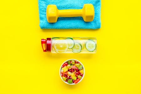 Photo pour Healthy lifestyle, healthy habits. Detox water, fruit salad, sport equipment dumbbells on yellow background top view. - image libre de droit