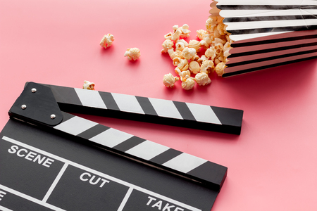 Photo pour Film watching concept. Clapperboard and popcorn on pink background copy space - image libre de droit