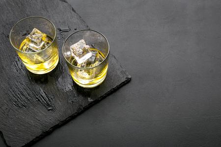 Foto de In the bar. Whiskey with ice on black desk on black background top view copy space - Imagen libre de derechos
