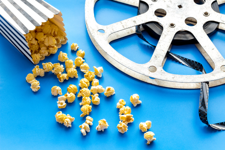 Photo for Cinema concept. film stock and popcorn on blue background - Royalty Free Image