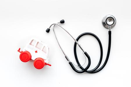 Foto de Ambulance service concept. Ambulance vehicle toy near stethoscope on white background top view. - Imagen libre de derechos