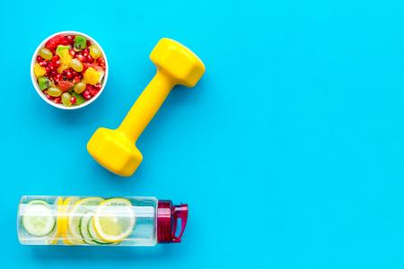 Photo pour Healthy lifestyle, healthy habits. Detox water, fruit salad, sport equipment dumbbells on blue background top view space for text - image libre de droit