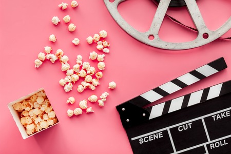 Photo for Movie premiere concept. Clapperboard, film stock, popcorn on pink background top view. - Royalty Free Image