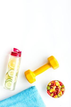 Photo pour Healthy lifestyle, healthy habits. Detox water, fruit salad, sport equipment dumbbells on white background top view. - image libre de droit