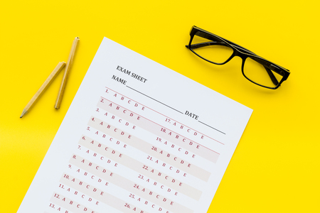 Photo pour On the exam. Exam sheet, answer near glasses and pencil on yellow background top view - image libre de droit