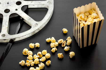 Foto de Cinema concept. film stock and popcorn on black background. - Imagen libre de derechos