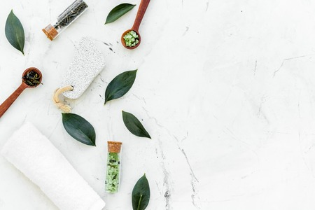 Photo pour Tea tree spa composition. Fresh tea tree leaves, natural cosmetics, towel on white stone background top view. - image libre de droit