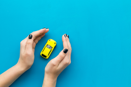 Foto de Car insurance concept. Safety of auto. Car toy in female hands on blue background top view. - Imagen libre de derechos