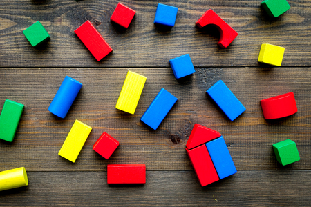 Photo pour Children background. Wooden building blocks for developing and entertainment on dark wooden background top view - image libre de droit