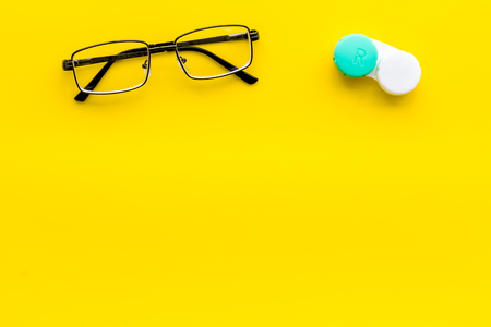 Photo for Eyes care. Glasses with transparent lenses and contact lenses on yellow background top view copy space - Royalty Free Image