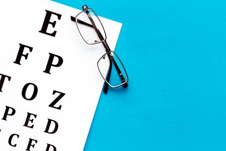 Foto de Eye examination. Eyesight test chart and glasses on blue background top view space for text - Imagen libre de derechos