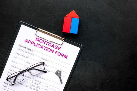 Photo pour Mortgage concept. Mortgage application form near key and house made of constructor on black background top view space for text - image libre de droit