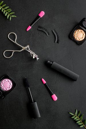 Photo pour Organic decorative cosmetic set with lash curler and mascara on black woman desk background top view. - image libre de droit
