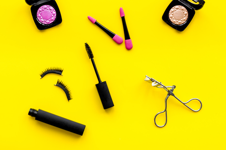 Photo pour Organic decorative cosmetic set with lash curler and mascara on yellow woman desk background top view. - image libre de droit
