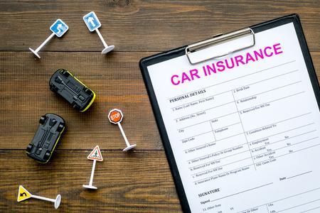 Photo pour Car insurance concept with form, car toys on wooden background top view - image libre de droit