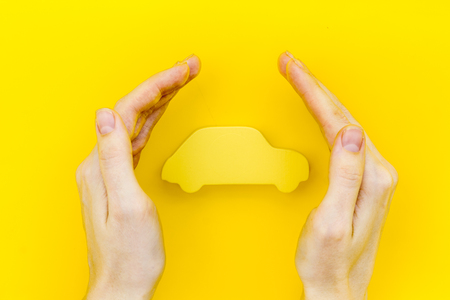 Photo pour Car buying and insurance concept with car figure in hands on yellow desk background top view - image libre de droit