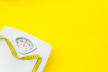 Foto de Diet. Bathroom scales and measuring tape for weight loss concept on yellow background top view mock up - Imagen libre de derechos