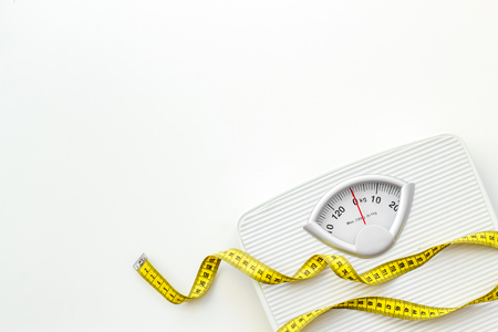Foto de Diet. Bathroom scales and measuring tape for weight loss concept on white background top view space for text - Imagen libre de derechos