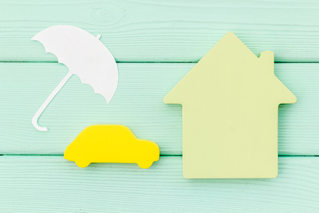 Photo pour buying new auto concept with car toy, house and umbrella figure on mint green wooden background top view - image libre de droit