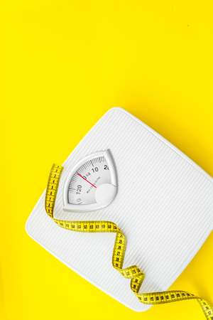 Foto de Proper nutrition. Medical starvation. Slim concept with scale and measuring tape on yellow background top view mockup - Imagen libre de derechos