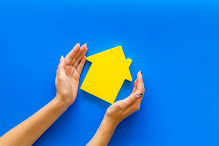 Photo for Search for a new house concept with house figure in hands on blue office desk background top view - Royalty Free Image
