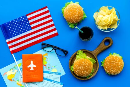 Photo for Gastronomical tourism concept with american flag, passport, tickets, map and food symbols, burgers, chips, coke on blue background top view - Royalty Free Image