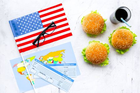 Photo for Gastronomical tourism concept with american flag, passport, tickets, map, glasses and food symbols, burgers, chips, cola on marble background top view - Royalty Free Image