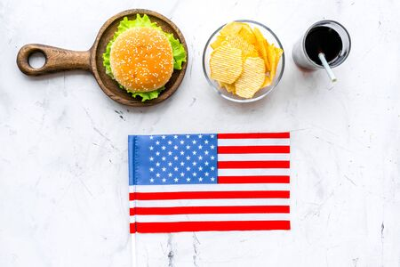 Photo for the 4th of July. Independence Day of America concept with flag, burgers, chips and cola on marble background top view - Royalty Free Image