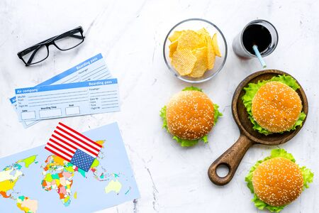 Photo for Gastronomical tourism with American flag, passport, tickets, map, burgers, chips, drink on marble background top view - Royalty Free Image
