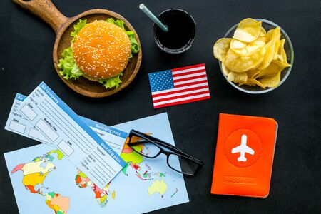 Photo for Gastronomical tourism with American flag, passport, tickets, map, burgers, chips, drink on black background top view - Royalty Free Image