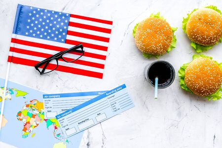Photo for Traditional food. Burger, map, tickets and USA flag for gastronomical tourism to America on marble background top view - Royalty Free Image