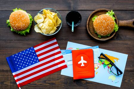 Photo for Traditional food. Burger, chips, map, tickets and USA flag for gastronomical tourism to America on wooden background top view - Royalty Free Image