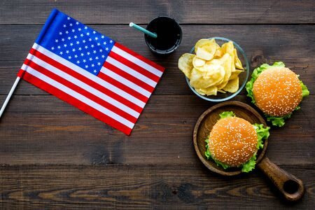 Photo for Independence Day of America celebration. Flag USA and national food, burgers, chips and drink on wooden background top view - Royalty Free Image