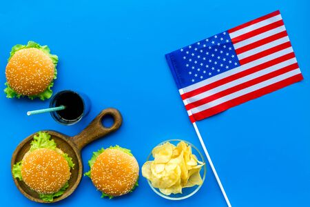 Photo for the 4th of July. Independence Day of America concept with flag, burgers, chips and drink on blue background top view - Royalty Free Image
