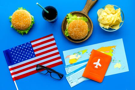Photo for Traditional food. Burger, chips, map, passport, tickets and USA flag for gastronomical tourism to America on blue background top view - Royalty Free Image