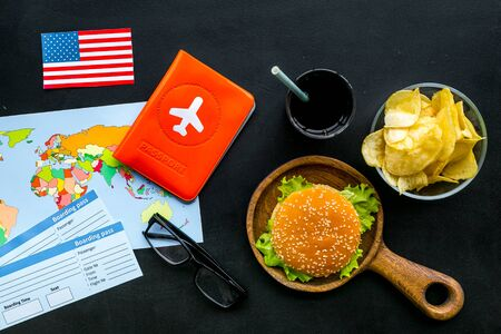 Photo for Gastronomical tourism concept with American flag, passport, tickets, map, glasses and food symbols, burgers, chips, drink on black background top view - Royalty Free Image