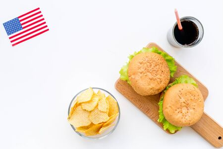 Photo for Independence Day of America celebration. Flag USA and national food, burgers, chips on white background top view - Royalty Free Image