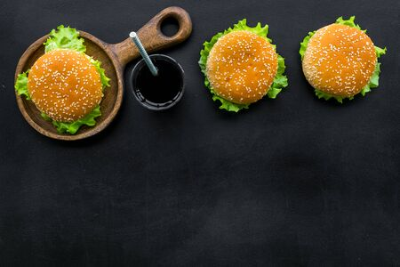 Photo for Traditional American food concept with burger on pan and drink on black background top view space for text. - Royalty Free Image