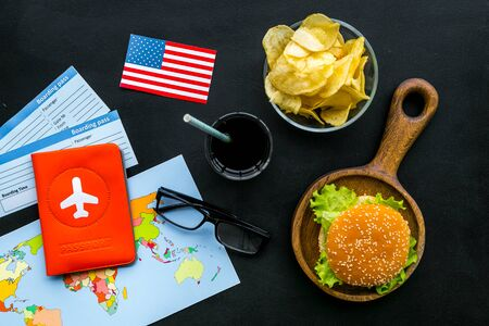 Photo for Traditional food. Burger, map, tickets, passport and USA flag for gastronomical tourism to America on black background top view - Royalty Free Image