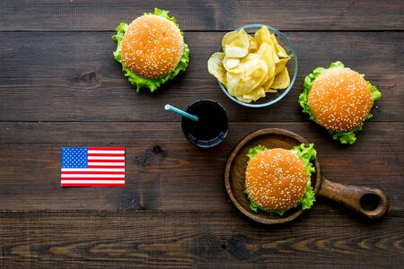 Photo for Independence Day of America concept with flag, burgers, chips and drink on wooden background top view - Royalty Free Image