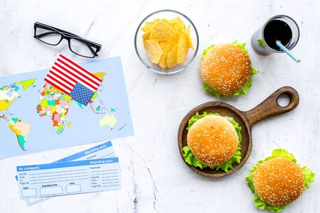 Photo for Gastronomical tourism concept with American flag, passport, tickets, map, glasses and food symbols, burgers, chips, drink on marble background top view - Royalty Free Image